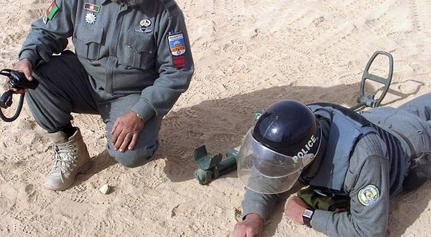 Two members of the Afghanistan National Police carrying out bomb disposal training drills (AP)