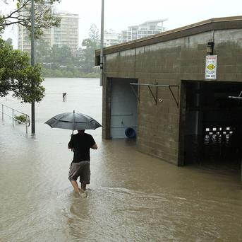 A resident walks past a flooded building after the Brisbane river burst its banks (AP)
