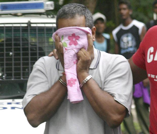 Suspect Sandip Moneea (41) covers his face as he is escorted to Mapou Court, Port Louis Mauritius, Wednesday, Jan. 12, 2011. The floor supervisor has been charged with the murder of Michaela McAreavey.