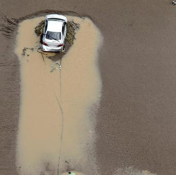 A vehicle is swept away in floodwaters in South East Queensland (AP)