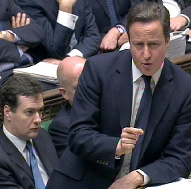 Prime Minister David Cameron speaks during Prime Minister's Questions as Chancellor George Osborne (left) looks on