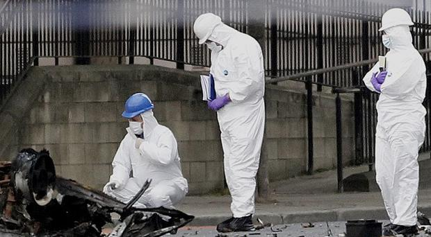 Forensic officers examine the remains of a car bomb outside Strand Road Police Station, Londonderry (AP)