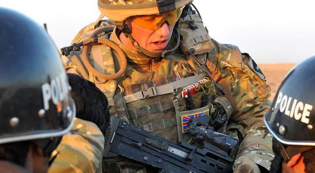 A British soldier briefs Afghan police officers after the arrest of five suspected poppy famers (AP)