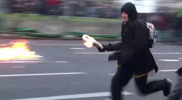 Police have released video footage of a man throwing a petrol bomb during the tuition fee protests