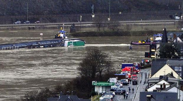 Tug boats secure a tanker carrying 2,400 tonnes of sulphuric acid after the barge capsized on the Rhine (AP)