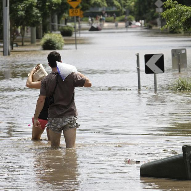 Residents walk through floodwater after getting ice and food to take to their flooded homes