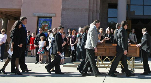 TUCSON, AZ - JANUARY 13: Pallbearers escort the casket of nine-year-old Christina Taylor Green into St. Elizabeth Ann Seton church on January 13, 2011 in Tucson, Arizona. Green was shot and killed during the January 8, shooting rampage of Jared Lee Loughner during a political event in Tucson. (Photo by Mamta Popat-Pool/Getty Images)