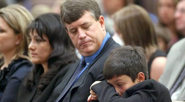 Brother Dallas Green wipes away a tear while seated next to his father John Green and mother Roxanna Green during the funeral service for their daughter nine-year-old Christina Taylor Green at St. Elizabeth Ann Seton church on January 13, 2011 in Tucson, Arizona.