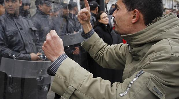 A protester faces police officers as he chants slogans against President Zine El Abidine Ben Ali in Tunis, Tunisia (AP)