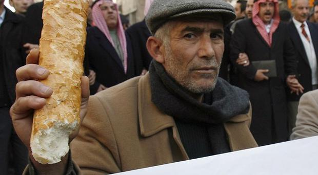 A Jordanian man brandishes a loaf of bread during a protest against rising food prices in Amman, Jordan (AP)