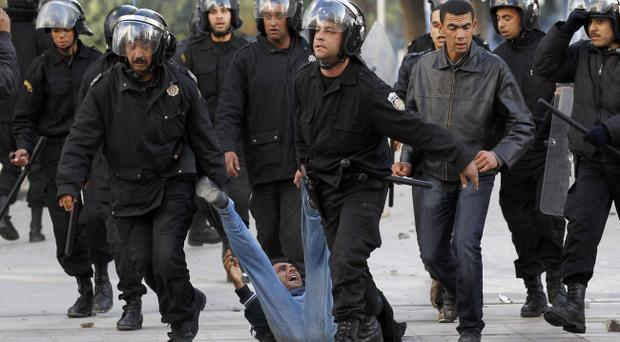 Riot police officers detain a protestor during clashes in Tunis, Friday, Jan. 14, 2011. Tunisia's president declared a state of emergency and announced that he would fire his government as violent protests escalated Friday, with gunfire echoing in the North African country's usually calm capital and police lobbing tear gas at protesters.