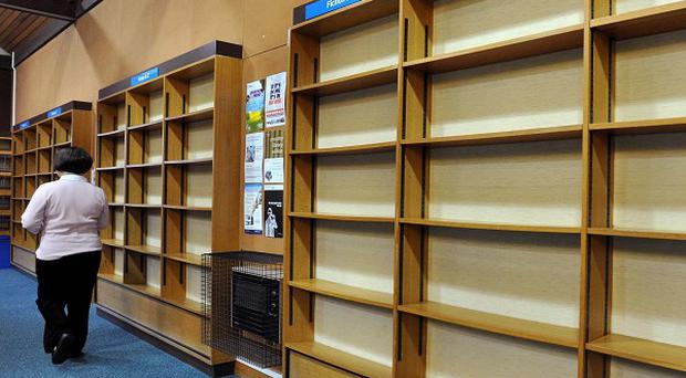 A person walks past empty shelves at the library in Stony Stratford, near Milton Keynes