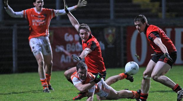 Down's Kevin Duffin (centre) tries to close down Armagh's Conor Clarke.