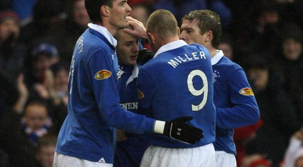 Kyle Lafferty (left) and Steven Davis (right) join Kenny Miller in congratulating two-goal hero Vladamir Weiss after his impressive display at Ibrox.