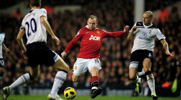 Wayne Rooney of Manchester United takes a shot on goal as Michael Dawson (L) and Alan Hutton (R) of Spurs close in during the Barclays Premier League match between Tottenham Hotspur and Manchester United at White Hart Lane.