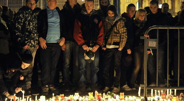 People light candles to mourn three young women who died in a stampede at a nightclub in downtown Budapest (AP)