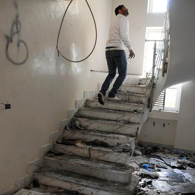 A man walks in the looted house of Mouez Trabelsi, the nephew of the former President's wife, Leila Ben Ali, in Marsa, Tunisia (AP)