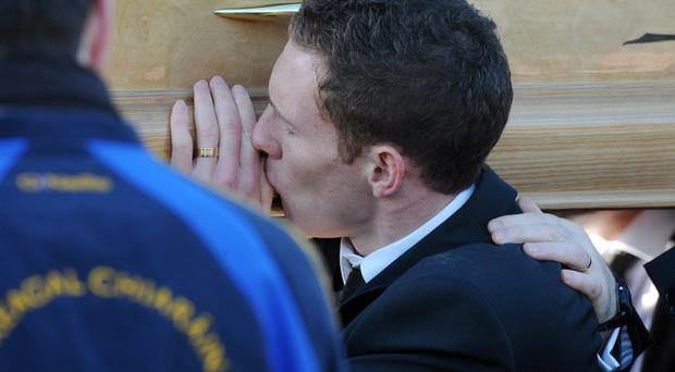 Michaela McAreavey's husband John kisses her coffin as her remains are carried to St Malachy's Church in Ballygawley for her funeral mass.