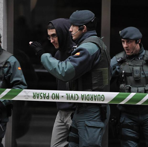 An alleged member of Ekin is escorted by Spanish Civil Guards as he leaves his home in northern Spain (AP)