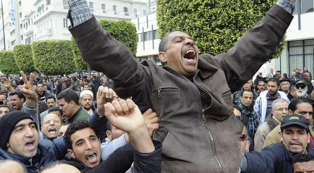 Protestors at a rally against the party of Ben Ali in the center of Tunis (AP)