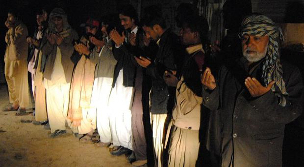 Pakistani residents praying outside their homes after a severe earthquake hit the south-west of the country (AP)