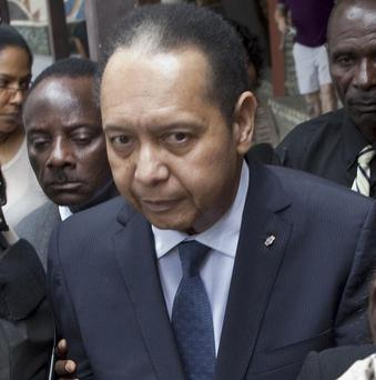 Ex-dictator Jean-Claude Duvalier, who faces corruption charges, is led out of his hotel by Haitian police (AP)