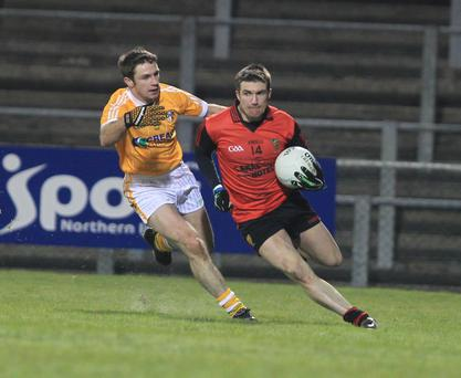 Antrim's Tony Scullion chases Down's Ronan Murtagh in last night's drawn match.