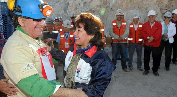 Jose Henriquez, left, greats an unidentified woman after being rescued from the collapsed San Jose gold and copper mine where he was trapped with 32 other miners for over two months near Copiapo, Chile