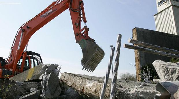 Diggers at work during the demolition of the exterior wall of the Maze Prison outside Lisburn