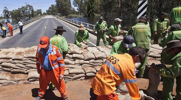Emergency workers pile sandbags on a bridge over the swollen Loddon River at Kerang (AP)