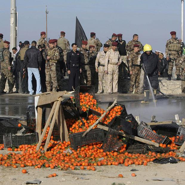 Iraqi security forces stand at the site of a bombing that also upturned a fruit stand in Karbala, Iraq (AP)
