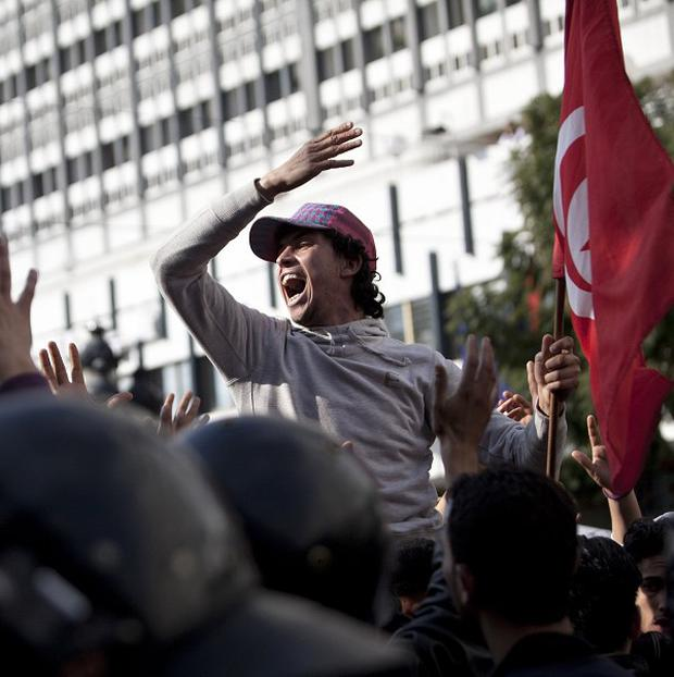 Protesters shout slogans during a demonstration against the RCD party of deposed president Zine El Abidine Ben Ali in Tunis (AP)