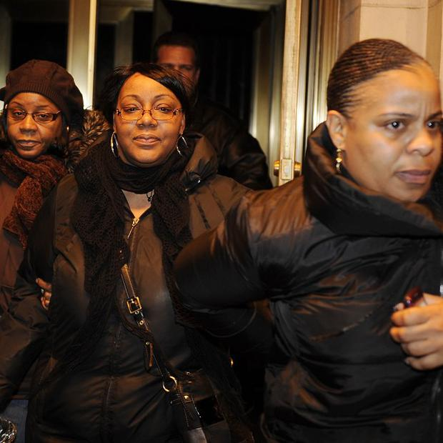 Joy White, centre, birth mother of Carlina White, exits a hotel with two unidentified women (AP)