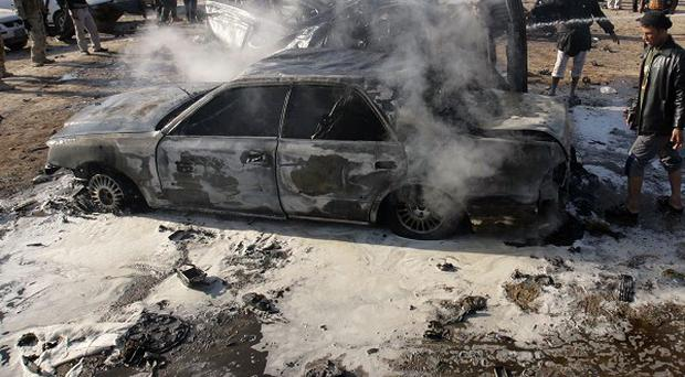 A destroyed car after a bombing in Karbala (AP)