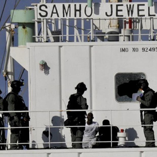 South Korean naval special forces stand guard over Somali pirates after detaining them on South Korean cargo ship Samho Jewelry