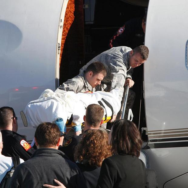 Gabrielle Giffords is loaded onto an airplane in Tucson, Arizona, as she is transferred to a rehabilitation center in Houston, Texas (AP)