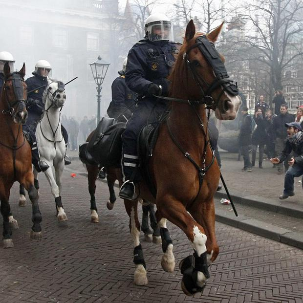 Police on horseback disperse a crowd of demonstrators opposed to education cuts outside the Dutch parliament (AP)
