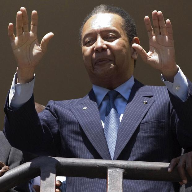 Haiti's former dictator Jean-Claude 'Baby Doc' Duvalier gestures to supporters on the balcony of his hotel room in Port-au-Prince, Haiti