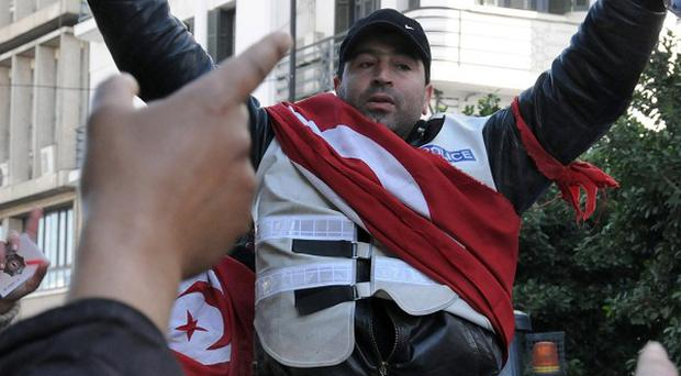 A police officer wrapped in the Tunisian flag and wearing a bullet-proof jacket shows the food policemen are given by their ministry (AP)
