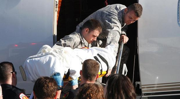 Gabrielle Giffords is loaded onto a plane in Tucson, Arizona, as she is transferred to a rehabilitation center in Texas (AP)