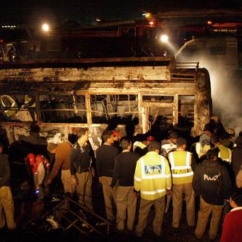 Police gather around a burnt-out bus after it collided with an oil tanker near Nooriabad in Pakistan (AP)