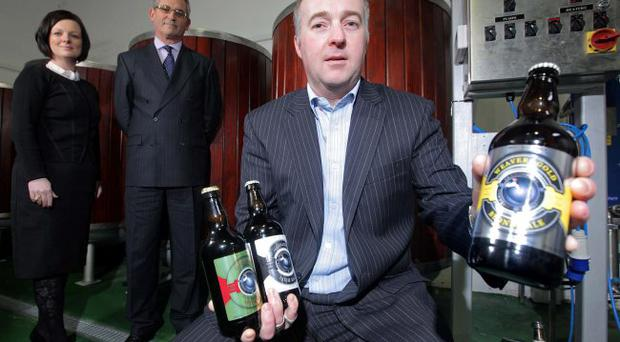 David Andrews and Lisa McCaul of Ulster Bank oversee Mark Pearson of Clanconnel brewery in Waringstown