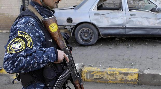 An Iraqi policeman stands in front a destroyed car after a bombing in Baghdad over the weekend (AP)