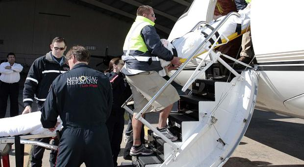Representative Gabrielle Giffords is carried from a plane after arriving in Houston to attend a rehabilitation centre (AP)