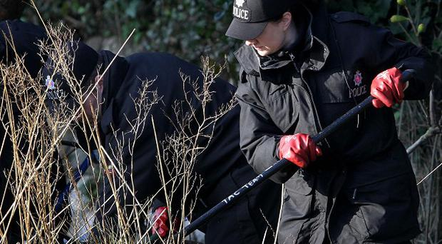 Police officers search undergrowth near the scene in Folkestone, Kent, where a man was stabbed to death