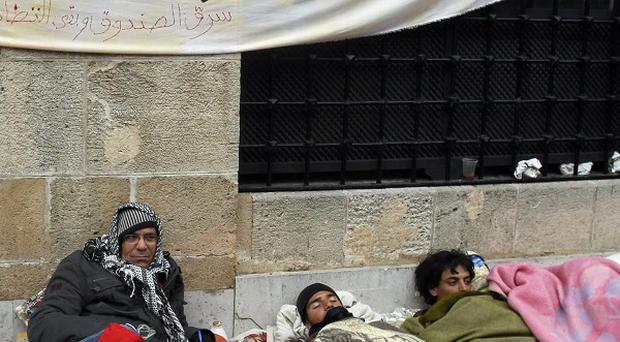 Protesters sit outside the prime minister's office in Tunis, demanding the removal of members of the ousted president's regime (AP)