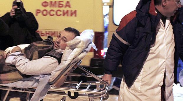 A wounded blast victim is brought by rescuers to a hospital from Domodedovo airport in Moscow (AP)