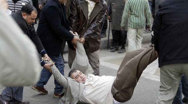 Plain clothes policemen arrest a man outside the journalists' syndicate in downtown Cairo (AP)