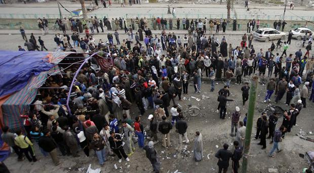 People gather at the scene of a car bomb attack at a funeral tent in Baghdad (AP)
