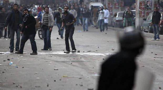 Egyptian anti-government activists throw stones on riot police during clashes in Cairo